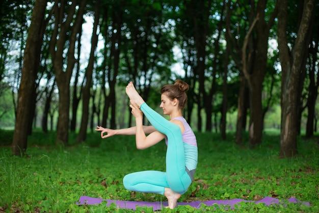 Szczupła brunetka uprawia sport i wykonuje piękne i wyrafinowane pozy jogi w letnim parku. zielony, bujny las na. kobieta robi ćwiczenia na matę do jogi