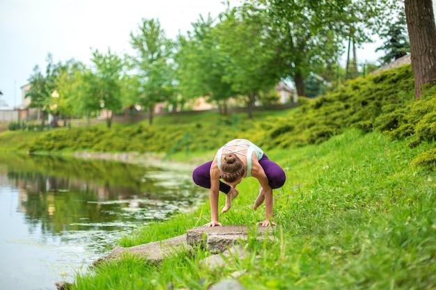 Szczupła brunetka uprawia sport i wykonuje piękne i wyrafinowane pozy jogi w letnim parku. zielony luksusowy las i rzeka w tle. kobieta robi ćwiczenia na matę do jogi