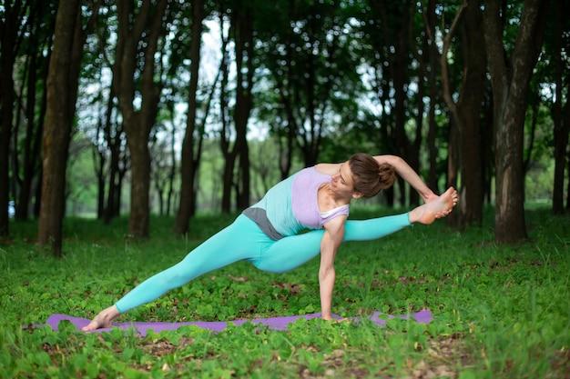 Szczupła brunetka uprawia sport i wykonuje piękne i wyrafinowane pozy jogi w letnim parku.