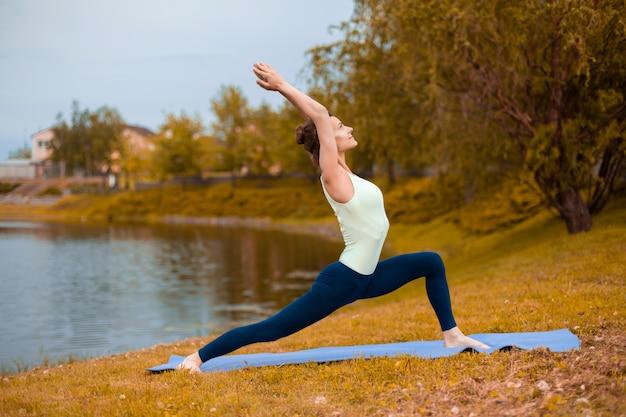 Szczupła brunetka uprawia sport i wykonuje pozy jogi jesienią nad jeziorem