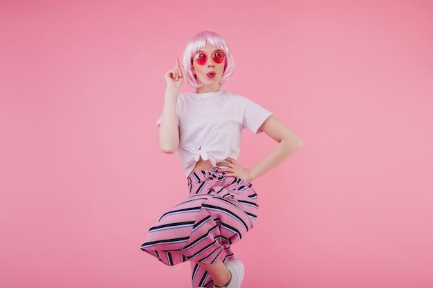 Szczupła, cudowna dziewczyna w letnich ubraniach i tańcząca na różowej ścianie peruke. elegancka europejska modelka w pasiastych spodniach chłodzi podczas sesji zdjęciowej