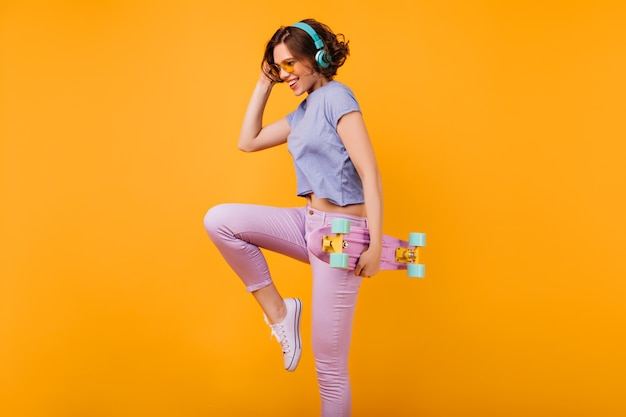Szczupła, czarująca dziewczyna w niebieskich słuchawkach tańczy z uśmiechem. zgrabna modelka z longboard skoki z radosną miną.