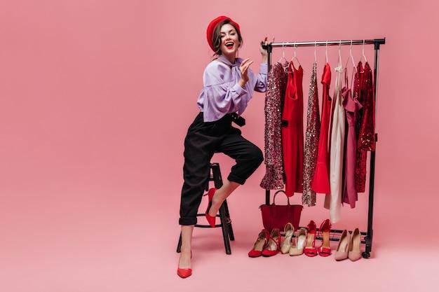 Szczupła dama w modnych spodniach, bluzce i czerwonej czapce siedzi na krześle obok stojaka z błyszczącymi sukienkami.