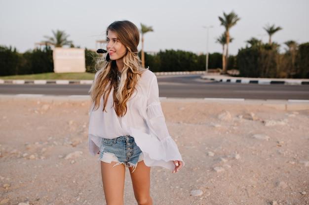 Szczupła, długowłosa kobieta w białej bluzce vintage, spacerująca po piasku z egzotycznymi palmami. urocza młoda kobieta z uroczą fryzurą spędza czas na zewnątrz i odwraca wzrok z zainteresowaniem