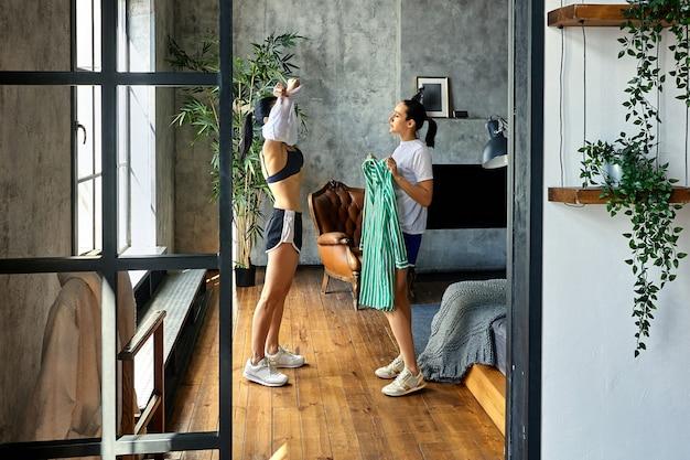Szczupła dojrzała kobieta przebiera się przy oknie w mieszkaniu na poddaszu, pomaga jej siostra