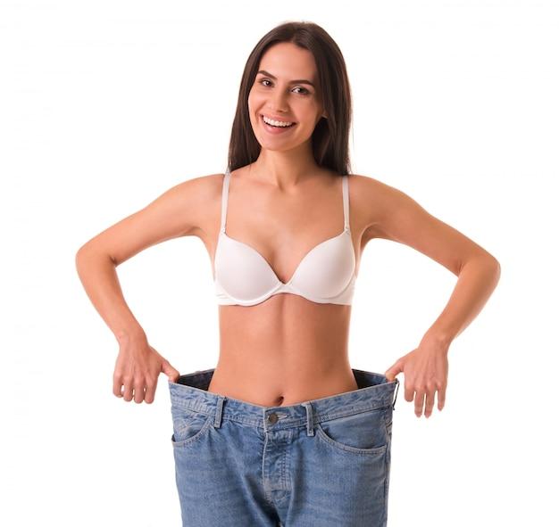 Szczupła dziewczyna ciągnie dżinsy i pokazuje utratę wagi.