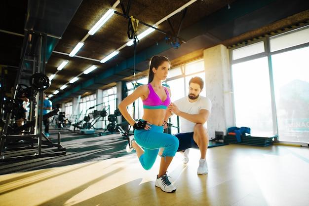 Szczupła dziewczyna fitness robi jedną nogę rozciągającą się z liny od góry i pomoc osobistego trenera na siłowni.