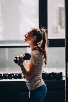 Szczupła dziewczyna lekkoatletycznego wykonuje ćwiczenia fizyczne z hantlami.