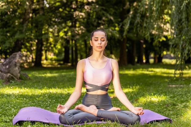 Szczupła dziewczyna medytuje siedząc w pozycji lotosu z zamkniętymi oczami na trawniku w parku