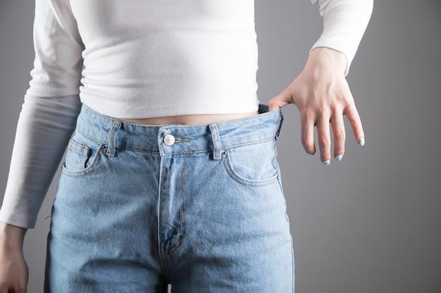 Szczupła dziewczyna nosi za duże spodnie na szarej scenie
