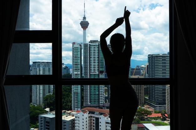 Szczupła dziewczyna patrzy na miasto przez duże okno. wysokie piętro.