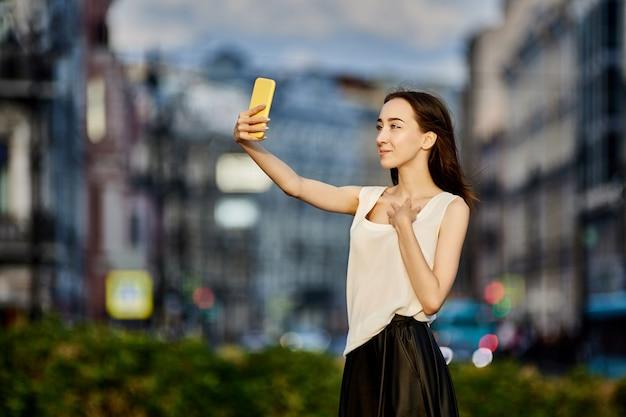 Szczupła dziewczyna robi selfie przez telefon komórkowy na zewnątrz