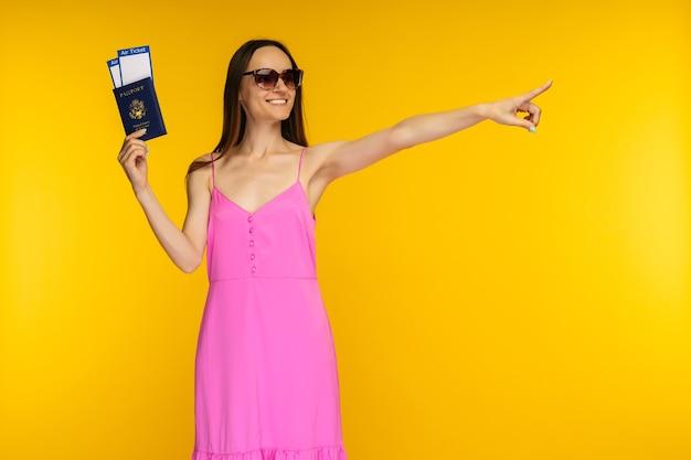 Szczupła dziewczyna trzyma paszport w różowej sukience i okularach przeciwsłonecznych