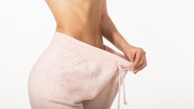 Szczupła dziewczyna ubrana w duże spodnie. kobieta pokazuje utratę wagi. dieta. koncepcja utraty wagi.