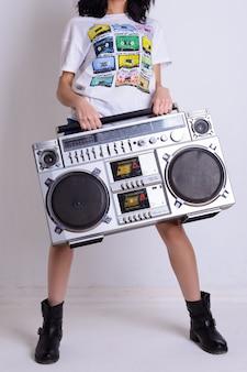 Szczupła dziewczyna w białej koszuli i czarnych butach trzyma stary magnetofon kasetowy