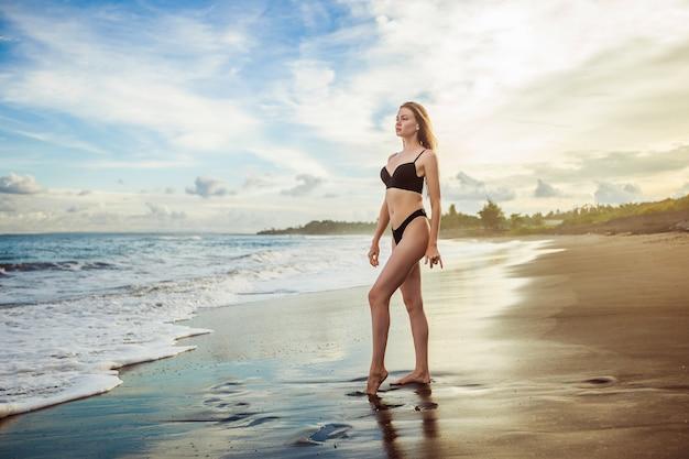 Szczupła dziewczyna w czarnym stroju kąpielowym stoi na plaży na tle pięknego zachodu słońca
