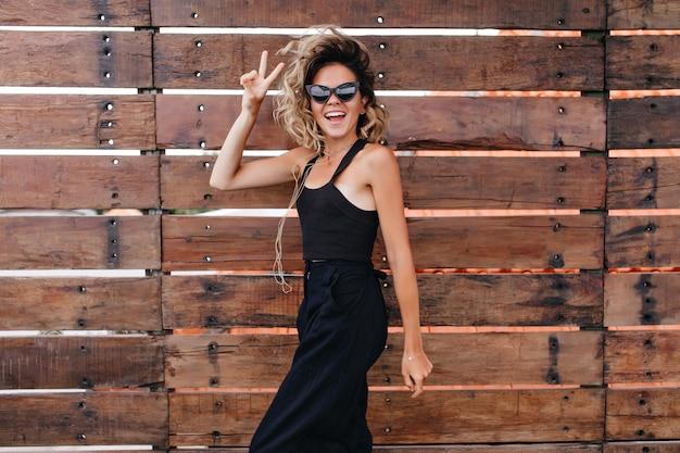 Szczupła dziewczyna w długim czarnym stroju wyrażająca radość w letni dzień. odkryty portret wyrafinowanej młodej kobiety w okularach przeciwsłonecznych, taniec na drewnianej ścianie.