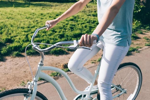 Szczupła dziewczyna w dżinsach i koszulce siedzi na niebieskim rowerze wycieczkowym w słoneczny poranek
