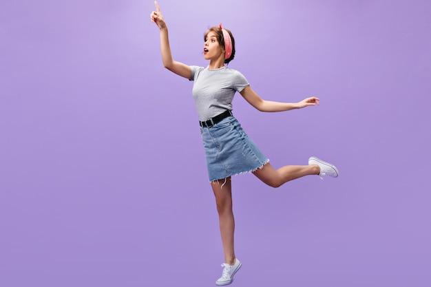 Szczupła dziewczyna w dżinsowym stroju pozowanie. n fioletowym tle. zaskoczona młoda dama z różową bandaną w białych tenisówkach i modnej skaczącej koszuli.