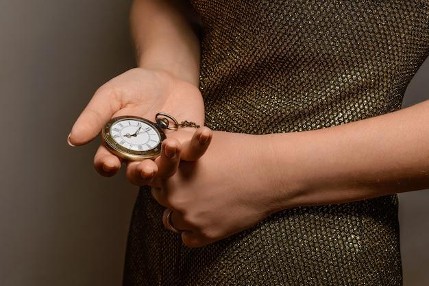 Szczupła dziewczyna w pięknej złotej sukni trzyma zegarek kieszonkowy vintage