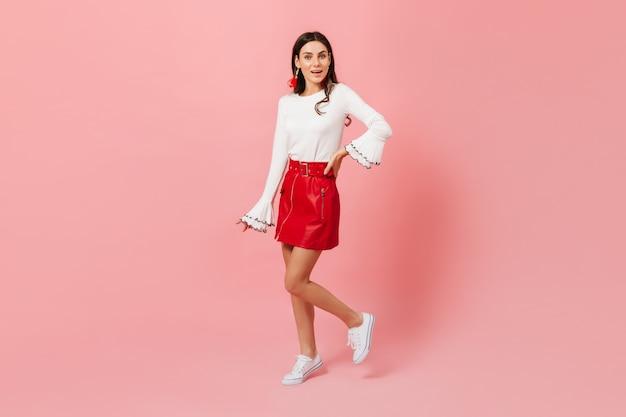 Szczupła dziewczyna w stylowy biało czerwony strój pozowanie na na białym tle. ujęcie brunetki w świetnym nastroju.