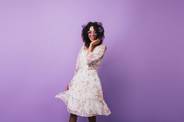 Szczupła dziewczyna z aliumami we włosach szczęśliwy taniec. przyjemna afrykańska młoda kobieta w sukienka vintage pozowanie.