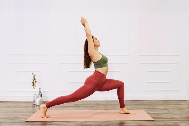 Szczupła fitness młoda kobieta praktykuje jogę relaksacyjną w domu. sport, zdrowy tryb życia
