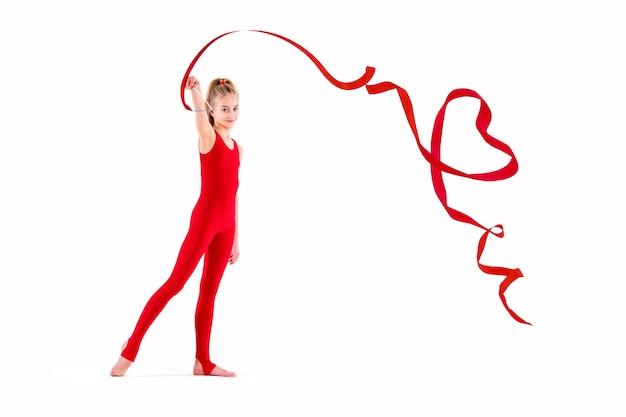 Szczupła gimnastyczka w czerwonym kombinezonie robi ćwiczenia ze wstążką na białym tle