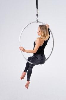 Szczupła i elastyczna dziewczyna w obręcz powietrzna na białym tle