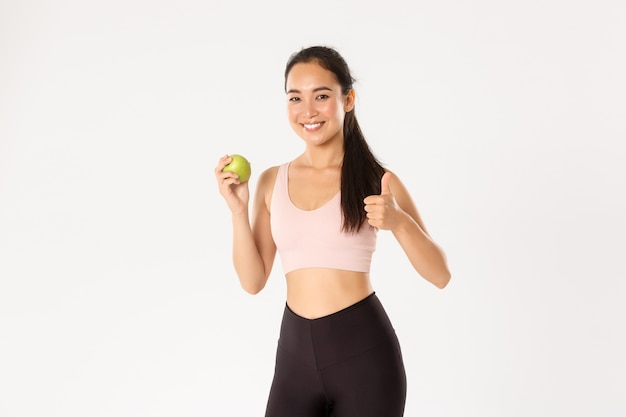 Szczupła i zdrowa urocza trenerka siłowni, trenerka fitness radzi jeść witaminy, pokazywać kciuki do góry i zielone jabłko, uśmiechnięta, zalecająca dietę.