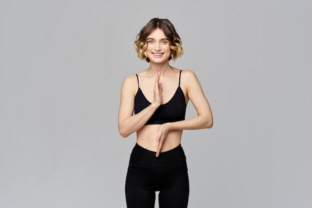 Szczupła kobieta gestykuluje rękami na szarej figurze sport fitness.