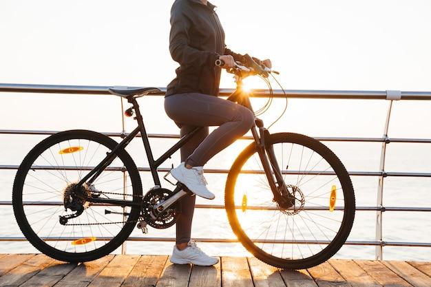 Szczupła kobieta jedzie na rowerze na promenadzie, podczas wschodu słońca nad morzem