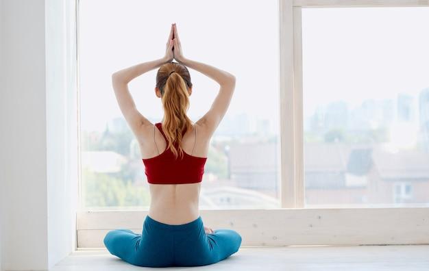 Szczupła kobieta medytuje na parapecie w stroju sportowym, widok z tyłu.