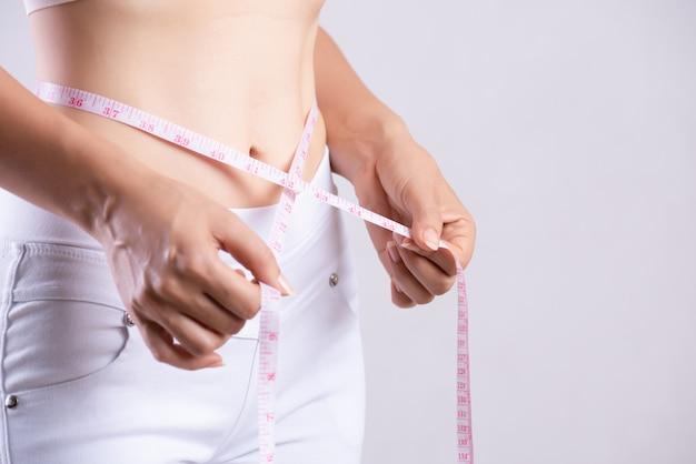Szczupła kobieta mierzy jej cienką talię z taśmy miarą. pojęcie opieki zdrowotnej