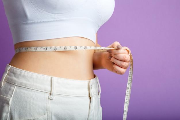 Szczupła kobieta mierzy talię miarką. zdrowe ciało kształtowanie koncepcji odchudzania. wąska talia mały brzuch w dużych białych spodniach dżinsowych na białym tle nad fioletowym kolorem tła. skopiuj miejsce