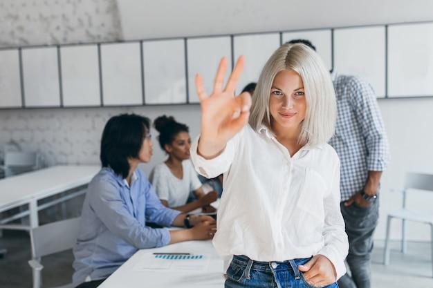 Szczupła kobieta o krótkich blond włosach pokazuje znak ok po udanych negocjacjach. portret azjatycki pracownik biurowy pozuje z afrykańskim kolegą podczas konferencji z jasnowłosą kobietą.