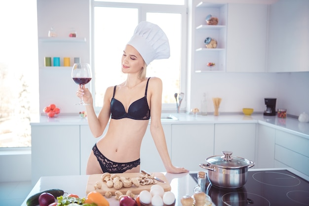 Szczupła kobieta pozuje w bieliźnie w kuchni
