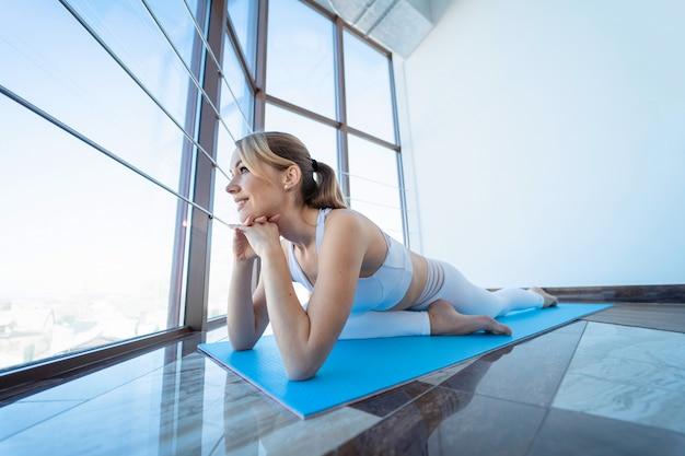 Szczupła kobieta robi joga siedząc w pozie gołębia