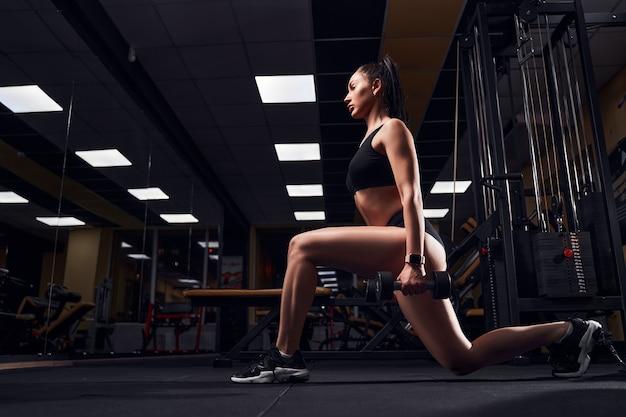 Szczupła kobieta robi rzuty z hantlami w dłoniach w nowoczesnej siłowni