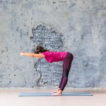 Szczupła kobieta robi sprawności fizycznej ćwiczeniu przeciw wietrzejącej szarości ścianie