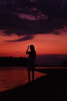 Szczupła kobieta stoi na plaży piękna młoda szczęśliwa kobieta podziwia zachód słońca i podnosi...