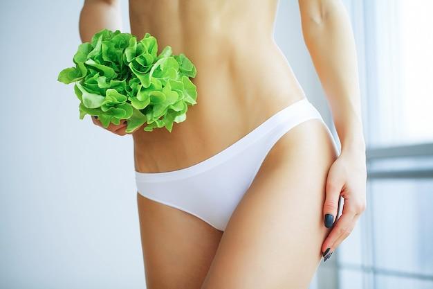 Szczupła kobieta trzyma w rękach świeżej zielonej sałatki
