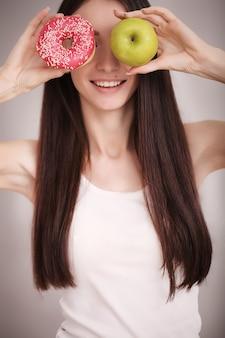 Szczupła kobieta trzymać w ręku różowy pączek i zielone jabłko