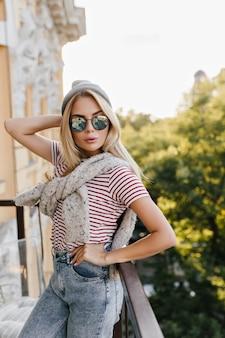 Szczupła kobieta w dżinsach i ciemnych okularach przeciwsłonecznych, odwracając wzrok stojąc na balkonie
