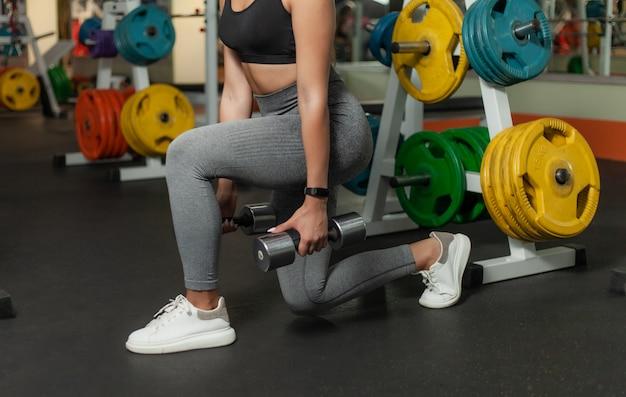 Szczupła kobieta w odzieży sportowej rzuca się na nogi z hantlami w dłoniach na siłowni. pojęcie zdrowego stylu życia