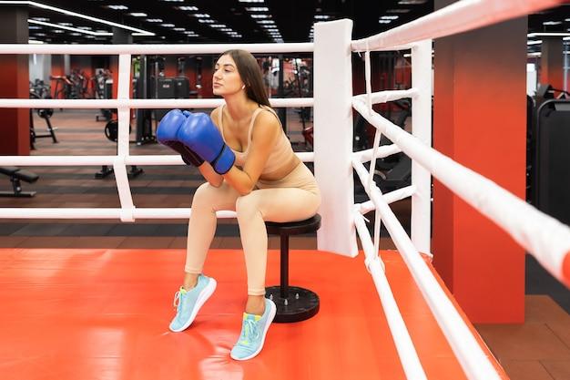 Szczupła kobieta w rękawicach bokserskich siedzi na ringu