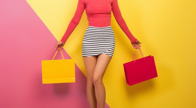 Szczupła kobieta w stylowym, kolorowym stroju trzymająca w rękach torby na zakupy, różowe żółte tło, mini spódniczka w paski, wyprzedaż, dyskoteka, zakupoholiczka, letni trend w modzie, detale, biodra