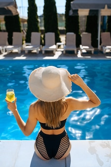 Szczupła kobieta z koktajl siedzi przy basenie w ośrodku, widok z tyłu. piękna dziewczyna relaksuje się przy basenie w słoneczny dzień, letnie wakacje atrakcyjnej osoby płci żeńskiej