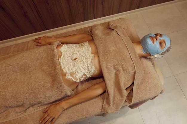 Szczupła kobieta z kremową maską na twarzy, leżąc na stole do masażu, widok z góry. masaż i relaks, pielęgnacja ciała i skóry. kobieta relaksuje się w salonie spa