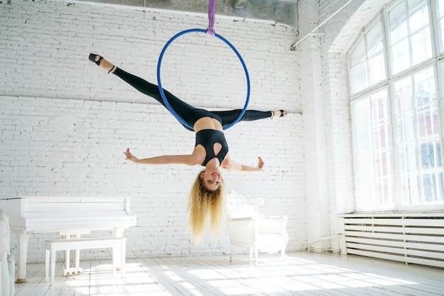 Szczupła kobieta zajmuje się gimnastyką powietrzną z kołem